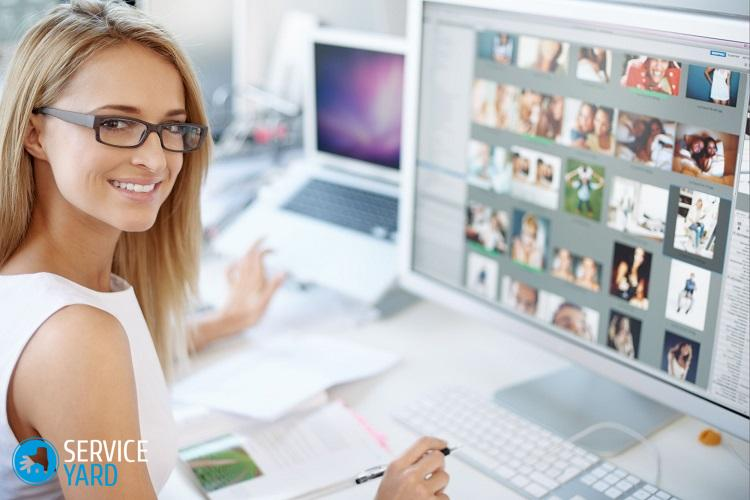 Portrait of young female designer sitting in office  with computer screen on front of her with images on